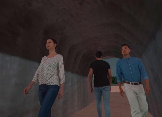 Escena dentro de un túnel con tres transeúntes, uno de espaldas y dos de cara.